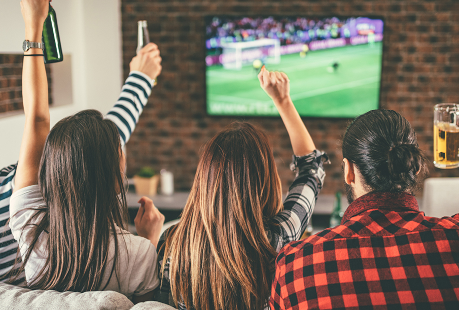 Group of friends watching sports with cable television