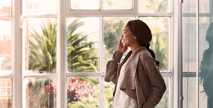 Woman talking on a landline phone at home