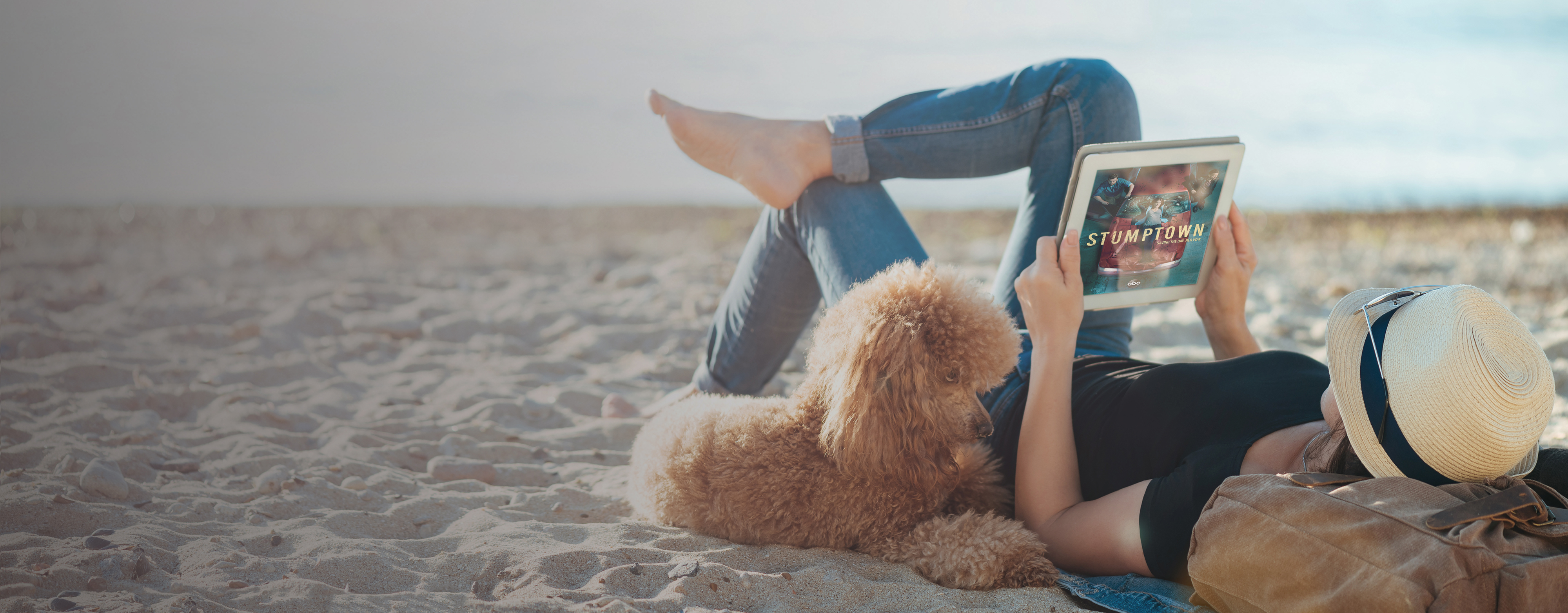Woman lying on beach with dog and watching TV Everywhere from Northland on tablet